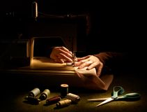 Sewing. Sewer hands with sewing machine and accessories on black background Stock Images