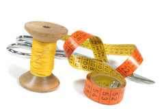 Sewing. Old bobbin with needle, measuring tape and Schrere on a white background stock image
