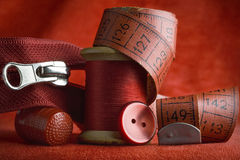 Sewing. All red sewing tools and items - spool of thread, thimble, zipper, measuring tape, button Stock Image