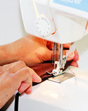 Sewing. Machine needle in motion while two hands are pulling garment being sewn Stock Photo