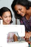 Sewing. Girl and mother using a sewing machine to make crafts Royalty Free Stock Image