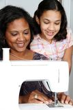 Sewing. Girl and mother using a sewing machine to make crafts Royalty Free Stock Photos