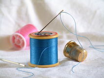 Sewing. Hand-sewing equipment including a thimble and threaded needle Royalty Free Stock Images