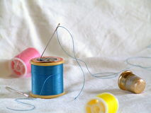 Sewing. Hand-sewing equipment including a thimble and threaded needle Stock Image