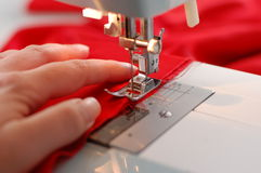 Sewing. A hand of a dressmaker supporting a cloth while sewing on a sewing machine Royalty Free Stock Photo