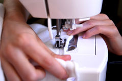 Sewing. Machine with young woman hands Royalty Free Stock Images