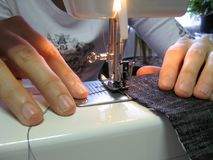 Sewing. The jeans by  machine, view close up Stock Images