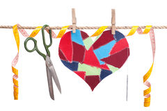 Sewing accessories. Fabric scraps heart and sewing accessories hanging on the clothesline. Isolated on white. Valentine\'s Day Royalty Free Stock Photos