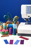 Sewing accessories in a basket and spools of threads next to sew Royalty Free Stock Images