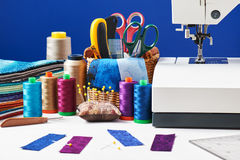 Sewing accessories in a basket and spools of threads next to sew. Ing machine stock photo