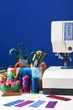 Sewing accessories in a basket and spools of threads next to sew Stock Image