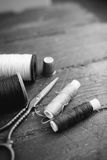 Sewing accessories: bobbins of thread, scissors, needle, thimble on wooden table. Black and white photo. Tailoring and Stock Images