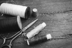 Sewing accessories: bobbins of thread, scissors, needle, thimble on wooden table. Black and white photo. Tailoring and Stock Image