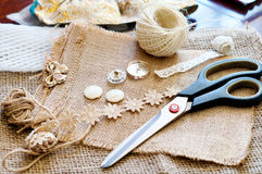 Sewing accessories on burlap. Rope, lace, buttons and scissors on burlap Stock Photography