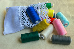 Sewing accessories. Coils yarns of different colors and white po Royalty Free Stock Images