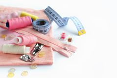 Sewing accessories and fabric on a white background. Pink fabric, sewing threads, needle, buttons and sewing centimeter royalty free stock photo