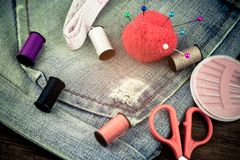 Sewing accessories on jeans background. Selective focus Royalty Free Stock Photo