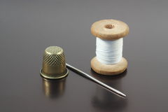 Sewing accessories. Old needle, thread and thimble on gray Royalty Free Stock Images