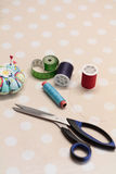 Sewing accessories and scissors. Pincushion, tape, thread and scissors on dotted tablecloth Royalty Free Stock Photography