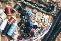 Sewing accessories - threads, buttons, zippers. On a light background Royalty Free Stock Photo
