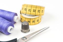 Sewing accessories and tools, medium purple sewing threads, yellow measuring tape with black numbers, scissors and metal thimble o. Sewing accessories and tools Royalty Free Stock Image