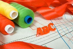 Sewing background:letters, threads, ribbon. Sewing background: ABC letters, threads and red ribbon Stock Image