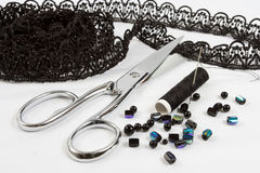 Sewing background: metal scissors,black threads. Monochrome sewing background: metal scissors,black threads, lace and beads Royalty Free Stock Photography