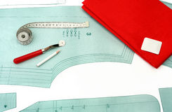 Sewing background. Sewing accessories and fabric on a paper pattern. Stock Image
