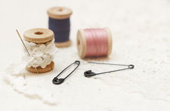 Sewing background. Spool of thread, lace and pins Stock Photography