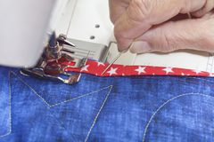 Sewing on  binding. A quilter sewing down binding to finished quilt Stock Photography