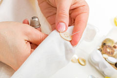 Sewing button on cloth Stock Photos