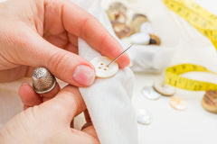 Sewing button on cloth Royalty Free Stock Photo