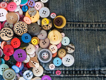 Sewing buttons on denim jeans Royalty Free Stock Image
