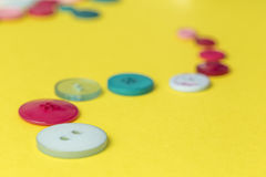 Sewing buttons in a row on yellow background Royalty Free Stock Images