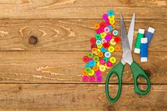 Sewing buttons, scissors and rolls of thread. On a wooden background royalty free stock photo