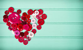 Sewing buttons in the shape of a heart Stock Image