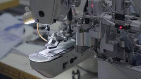 Sewing buttons on shirts at the special automated typing machine. That itself submits and sews buttons stock footage