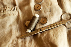 Sewing. Buttons, thread, needle and scissors lying on the fabric Stock Photography