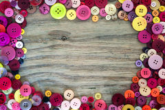 Sewing buttons on wood background Royalty Free Stock Images