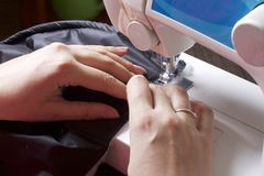 Sewing clothes by an individual entrepreneur. A woman is working on a sewing machine. Staples the cut elements of the product. Stock Images