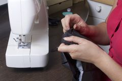 Sewing clothes by an individual entrepreneur. A woman is working on a sewing machine. Staples the cut elements of the product. Sewing clothes by an individual Royalty Free Stock Photography