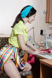 Sewing clothes in workshop: beautiful brunette young woman pinup girl with red lips and nails blue ribbon Stock Photos