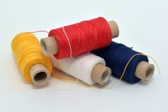 Sewing colored threads: yellow, red, dark blue, white. stock image