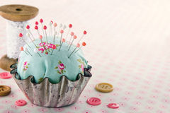 Sewing concept background with floral pincushion. Green handmade floral pincushion in an old metal cupcake with buttons and spools of thread and lace, sewing Royalty Free Stock Photo