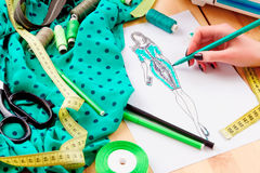 Sewing concept. Dressmaker. Dressmaker`s workplace: scissors, ribbons, lace, pencils, sketch, fabric, measuring tape and band. Girl sketching a dress royalty free stock images