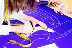 Sewing concept. Dressmaker. Workplace of a dressmaker: scissors, pattern, needles, textile, sewing spools and measure tape. Girl drawing a pattern for the dress stock photography