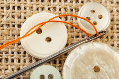 Sewing concept. Needle with thread and snaps close up on burlap background Royalty Free Stock Images