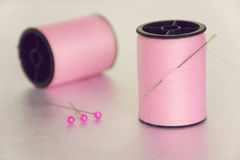 Sewing Concept. Two spools of pink thread with one with a sewing needle stuck in it Stock Images