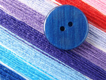 Sewing design. Button with colorful sewing threads Royalty Free Stock Image