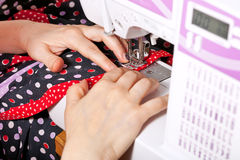 Sewing dress on machine Stock Photo